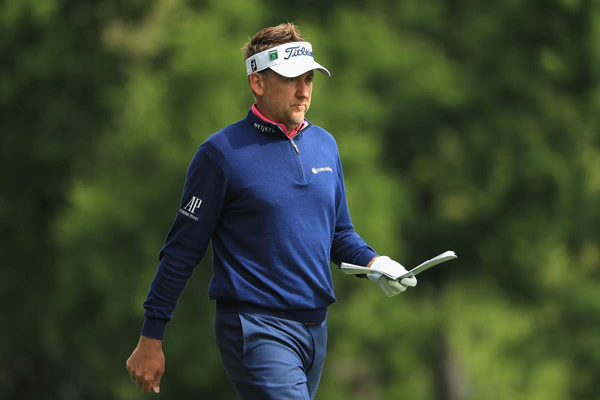 Ian Poulter consults his yardage book.